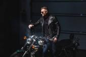 módní chlap v černé sluneční brýle, stojící na motocyklu v garáži