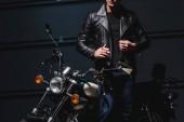 Fotografia vista potata del ragazzo in piedi in moto nel garage