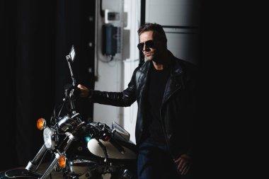Stylish man in black sunglasses posing by motorbike in garage stock vector