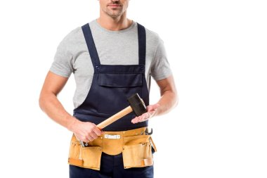 Partial view of worker in overalls holding hammer isolated on white stock vector
