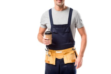 Partial view of worker with tool belt drinking coffee to go isolated on white stock vector
