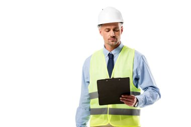 Focused engineer in helmet looking at clipboard isolated on white stock vector