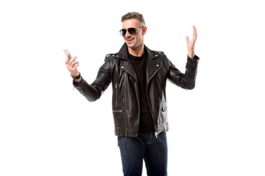 excited handsome man in sunglasses using smartphone isolated on white