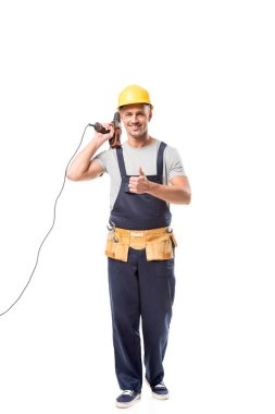 Smiling construction worker holding drill and doing thumb up isolated on white stock vector