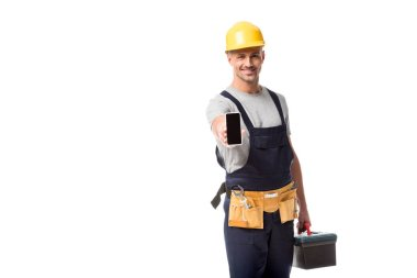 construction worker in hard hat presenting smartphone with blank screen isolated on white