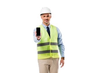 Smiling engineer looking at camera and holding smartphone with blank screen isolated on white stock vector