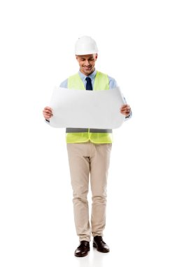 Smiling engineer in helmet looking at blueprint isolated on white stock vector