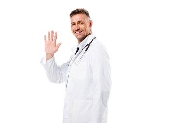 Handsome doctor waving and looking at camera isolated on white stock vector