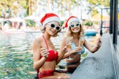 portrait of smiling women in santa caus hats with fireworks and glasses of champagne resting in swimming pool, new year and christmas celebration concept