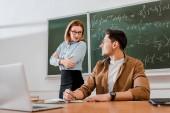 Ženské profesor stojící s překřížením rukou a při pohledu na studentů ve třídě