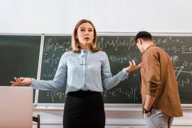 Female teacher gesturing in classroom in formalwear near student