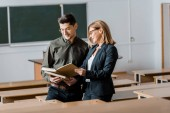 Fotografie male student and female teacher in formal wear looking at university books in classroom