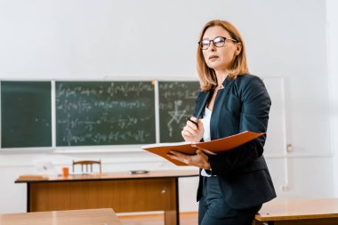beautiful female teacher in formal wear and glasses holding notebook in classroom