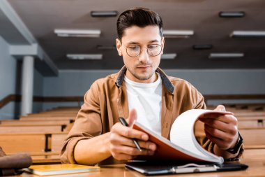 concentrated male student in glasses sitting at desk and holding notebook with pen in classroom