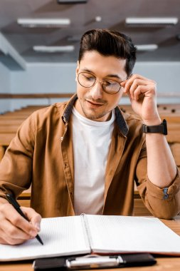 concentrated male student in glasses sitting at desk and writing in notebook during lesson in classroom