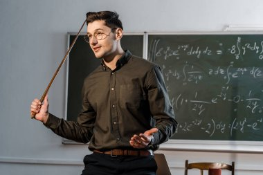 handsome male teacher in formal wear holding wooden pointer and explaining equations in class
