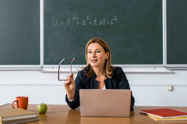 female teacher sitting at computer desk, holding glasses and talking in classroom
