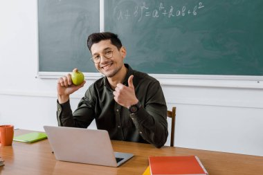 male teacher in glasses looking at camera, holding apple and showing thumb up sign at computer desk in classroom