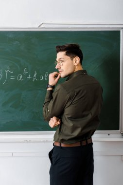 pensive male teacher touching chin and solving equation on chalkboard in class