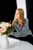 attractive young female photographer arranging flowers in photo studio