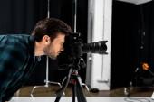 Fotografia vista laterale del giovane fotografo che lavora con la macchina fotografica professionale in studio