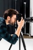 boční pohled pohledný mladý fotograf pracuje s profesionálním fotoaparátem ve studiu