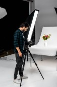 Fotografie handsome young photographer shooting beautiful flowers in professional photo studio