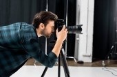 side view of professional young photographer working with camera in photo studio