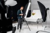 Fotografia bello giovane fotografo lavorando con la macchina fotografica e apparecchi di illuminazione in studio fotografico