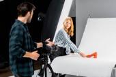 Fotografia Fotografo maschio in piedi con la macchina fotografica ed esamina collega organizzare scarpa in studio