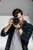 schöner junger männlicher Fotograf mit professioneller Kamera im Fotostudio