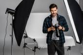 csinos fiatal fotós mosolyogva fényképezőgép fotó stúdió munka közben