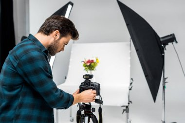 young photographer photographing beautiful flowers in professional photo studio