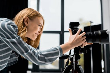 Side view of smiling young female photographer working with professional photo camera in studio stock vector