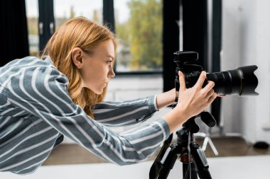 side view of young female photographer working with professional photo camera in studio