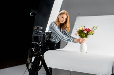 close-up view of photo camera and female photographer arranging flowers in studio