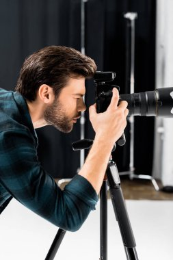 Side view of handsome young photographer working with professional photo camera in studio stock vector