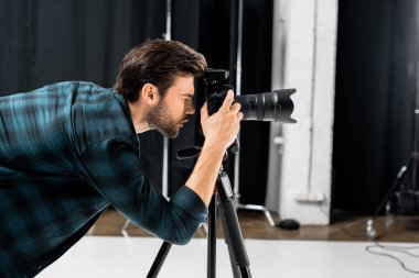 Side view of professional young photographer working with camera in photo studio stock vector