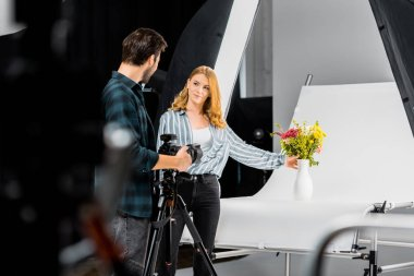 selective focus of young photographers looking at each other while shooting flowers in studio