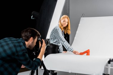 male photographer working with camera while colleague arranging shoe in studio