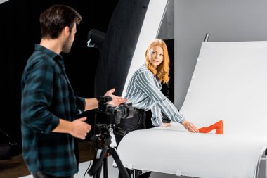 male photographer standing with camera and looking at colleague arranging shoe in studio