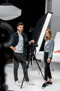 happy young photographers standing together and smiling at camera in photo studio