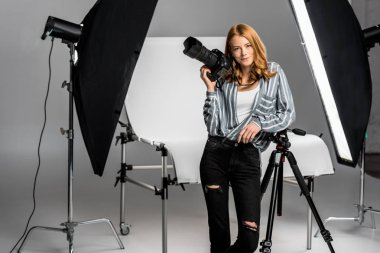 attractive young female photographer working in professional photo studio