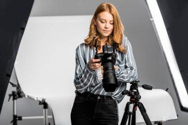 Beautiful young woman using photo camera in studio stock vector