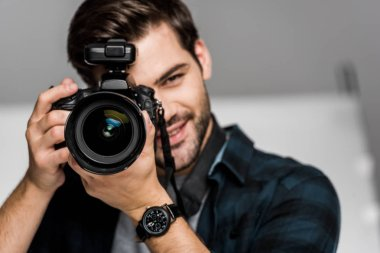 Smiling young man photographing with camera in studio stock vector