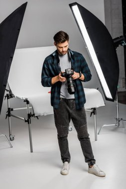 Full length view of handsome professional young photographer using camera in photo studio stock vector