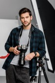 hezký profesionální mladý fotograf při pohledu na fotoaparát ve fotoateliéru