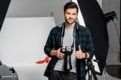 handsome smiling young photographer holding camera and showing thumb up in studio