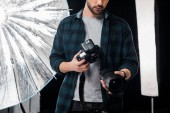 cropped shot of young photographer holding photo camera and lens in studio