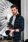 Fotografie hezký profesionální mladý fotograf držení fotoaparátu a objektivu ve studiu